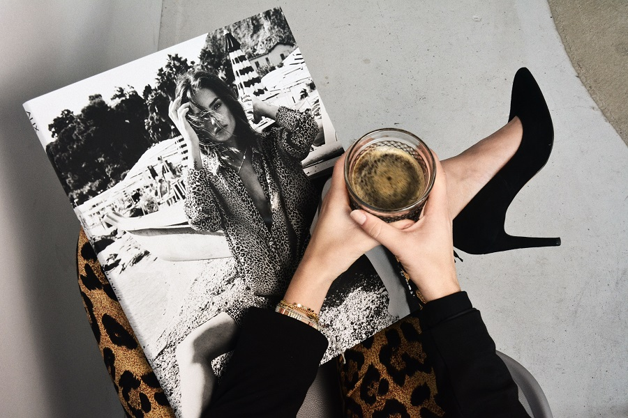 Ergänzung zum Text: FRau mit Getränk und Modezeitschrift auf den Knien