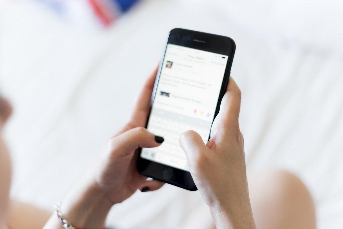 Minimalismus Apps: Frau mit schwarz lackierten Fingelnägeln tippt auf dem Smartphone