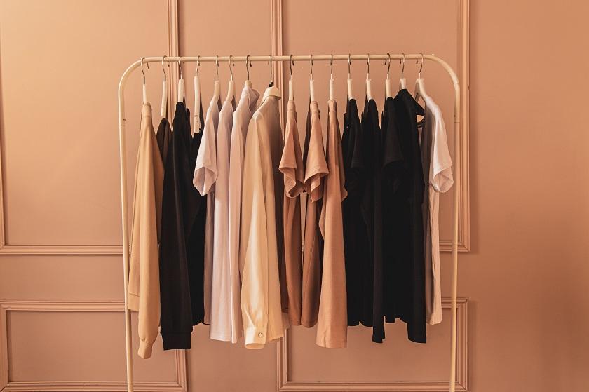 Minimalistischer Kleiderschrank - bronze und rosefarbene Kleidung hängt auf Kleiderstange