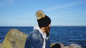 Zur Ergänzung des Textes. Autorin sitzt am Strand und blickt aufs Wasser.