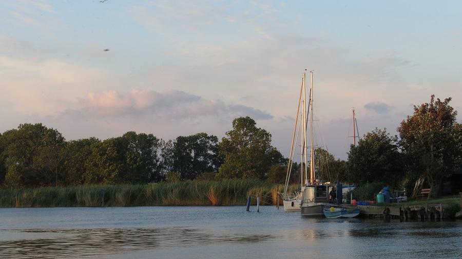 Auf der Karte von Usedom liegt Wilhelmshof am Rand; Foto zeigt Segelboot bei Sonnenuntergang
